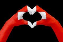 La bandiera delle mani della Svizzera, modella un cuore Concetto del simbolo del paese, isolato sul nero Immagini Stock