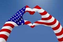 La bandiera delle mani di U.S.A., modella un cuore Concetto del simbolo del paese, su cielo blu Fotografie Stock Libere da Diritti