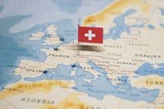 La bandiera dello svizzero nella mappa di mondo fotografia stock libera da diritti