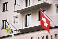 La bandiera dello svizzero sulla parte anteriore di costruzione compera nel villaggio di Samnaun Fotografia Stock