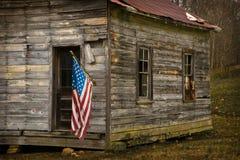 La bandiera di U.S.A. pende da un vecchio orizzontale della cabina Fotografia Stock