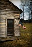 La bandiera di U.S.A. pende da una vecchia cabina Fotografia Stock Libera da Diritti