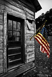 La bandiera di U.S.A. pende da una vecchia spruzzata di colore della cabina Fotografie Stock