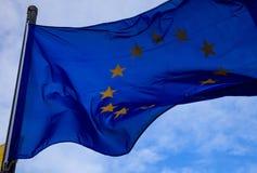 La bandiera di Unione Europea ondeggia sull'asta della bandiera, con cielo blu e le nuvole per fondo Primo piano con il dettaglio Immagini Stock Libere da Diritti