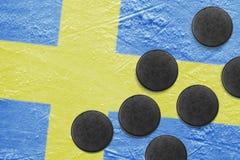 La bandiera e le rondelle svedesi sul ghiaccio Immagine Stock Libera da Diritti