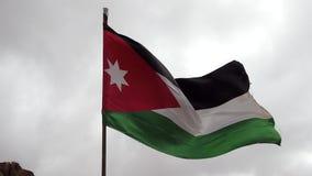 La bandiera giordana vola nel movimento lento 1 del vento rigido stock footage