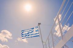 La bandiera greca sulla nave contro il cielo ed il sole fotografie stock