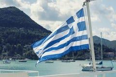 La bandiera greca sulla nave contro lo sfondo del mare delle isole Viaggio del mare nel mare ionico immagine stock libera da diritti