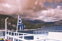 La bandiera greca sulla nave contro lo sfondo del mare delle isole Viaggio del mare nel mare ionico fotografia stock
