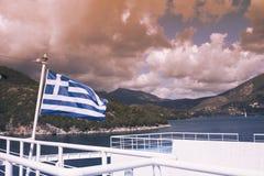 La bandiera greca sulla nave contro lo sfondo del mare delle isole Viaggio del mare nel mare ionico immagini stock libere da diritti