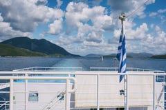 La bandiera greca sulla nave contro lo sfondo del mare delle isole Viaggio del mare nel mare ionico immagine stock