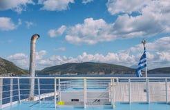 La bandiera greca sulla nave contro lo sfondo del mare delle isole Viaggio del mare nel mare ionico fotografia stock libera da diritti