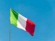 La bandiera italiana che ondeggia sopra un cielo blu Immagini Stock