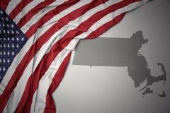 La bandiera nazionale d'ondeggiamento degli Stati Uniti d'America su un Massachusetts grigio indica il fondo della mappa Fotografie Stock Libere da Diritti