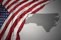 La bandiera nazionale d'ondeggiamento degli Stati Uniti d'America su un North Carolina grigio indica il fondo della mappa fotografie stock libere da diritti