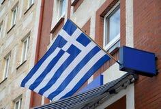 La bandiera nazionale della Repubblica Ellenica fluttua su una facciata della costruzione Fotografie Stock