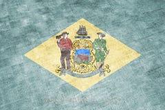 La bandiera nazionale dello stato USA Delaware dentro contro uno straccio grigio del tessuto il giorno di indipendenza nei colori illustrazione di stock