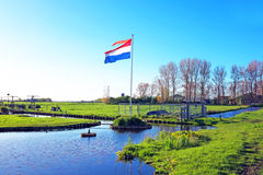 La bandiera nazionale olandese in un paesaggio olandese Fotografia Stock