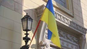 La bandiera nazionale ucraina fluttua sopra l'entrata al seggio elettorale Elezioni presidenziali in Ucraina archivi video