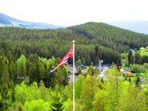 La bandiera norvegese in un briciolo dello stendardo un pezzo del villaggio nel fondo fotografia stock