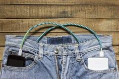 La banque de puissance se situe dans une poche arrière de jeans, dans l'autre est une foule Photographie stock
