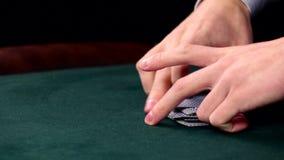 La barajadura del crupié carda, muestra uno en la tabla verde en el casino almacen de video