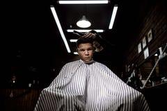 La barbería elegante El peluquero de la moda hace un peinado elegante para un hombre negro-cabelludo que se sienta en la butaca imagen de archivo libre de regalías