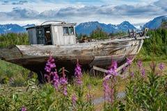 La barca abbandonata si siede in un rottamaio lungo l'Alaska Homer Spit un giorno di estate soleggiato immagini stock