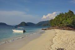 La barca alla spiaggia in tropici Fotografia Stock