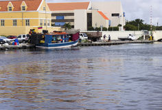 La barca blu ha attraccato dietro le costruzioni variopinte iconiche del Curacao Immagine Stock Libera da Diritti