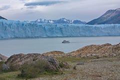 La barca che galleggia prima di un ghiacciaio di Perito Moreno Fotografie Stock Libere da Diritti
