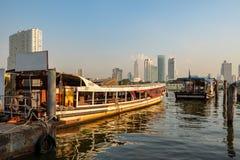 La barca della navetta al pilastro con la vista della città ed il chiaro fondo del cielo blu immagine stock libera da diritti