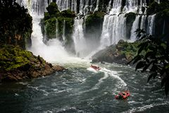 La barca della velocità guida sotto l'acqua che precipita a cascata durante le cadute di Iguacu fotografia stock