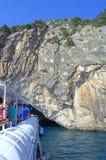 La barca di crociera entra nella caverna del mare Fotografie Stock