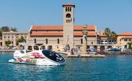 La barca di escursione sta guidando lungo la vecchia torre veneziana dell'orologio al vecchio porto marittimo dell'isola di Rodi, Fotografia Stock