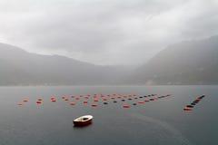 La barca ed i galleggianti su una cozza coltivano nella pioggia Fotografia Stock