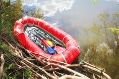 La barca gonfiabile rossa con i remi trasporta per trasportare lungo un fiume fotografie stock