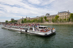La barca ha ammucchiato con i turisti che fanno un giro turistico lungo la Senna a Parigi Immagine Stock Libera da Diritti