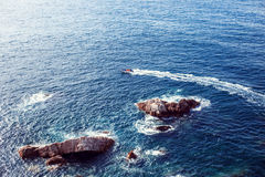 La barca naviga vicino alle rocce nell'acqua e riserva il percorso dell'acqua Fotografia Stock