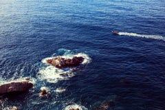 La barca naviga vicino alle rocce nell'acqua e riserva il percorso dell'acqua Immagine Stock