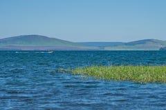 La barca si precipita lungo il lago contro il contesto delle montagne, con una canna nella priorità alta Immagini Stock