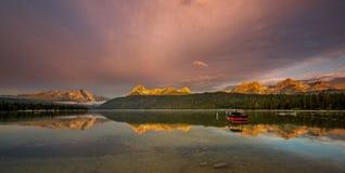 La barca su un lago come la luce di mattina colpisce le cime dell'alta montagna fotografia stock