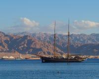 La barca a vela con i turisti è in rosso mare contro le montagne ed il porto di Aqaba immagini stock libere da diritti