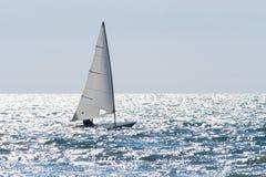 La barca a vela naviga su un mare scintillante in un giorno ventoso Immagine Stock