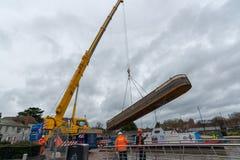 La barge de travail s'est abaissée par la grue jaune dans le canal Photographie stock libre de droits