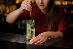 La barmaid avec la manucure rose mélange un mojito alcoolique de cocktail à une cuillère image stock