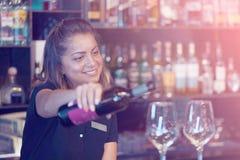 La barmaid de fille verse le vin dans un verre de vin photos stock