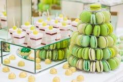 La barra de caramelo con los macarons, tortas, pasteles de queso, torta hace estallar Pyramide verde colorido de los macarrones imágenes de archivo libres de regalías