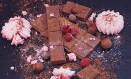La barra de chocolate junta las piezas y los cubos en fondo del darck, la visión superior con los merengues y las frambuesas imágenes de archivo libres de regalías