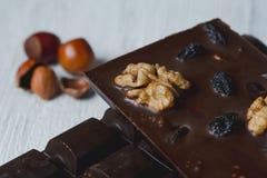 La barra de chocolate llenó de diversas bayas y del primer nuts l Foto de archivo